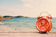 Alarm clock on table and sea background Royalty Free Stock Images