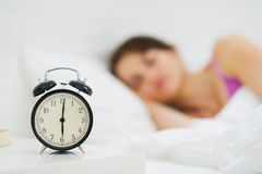 Alarm clock on table and woman in background royalty free stock photos