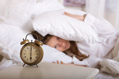 Alarm clock on table and woman sleeping Royalty Free Stock Photos