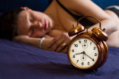 Alarm clock on table and woman sleeping Royalty Free Stock Photo