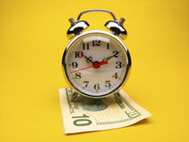 Alarm clock on ten dollar ball Stock Photography