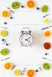 Alarm clock - time to breakfast with fruits, mock-up Royalty Free Stock Photos