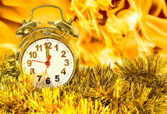 Alarm clock in the tinsel against the flames Stock Photos