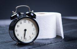 Alarm clock with toilet paper on a table Stock Photo