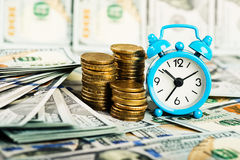 Alarm clock on top of pile of banknote Stock Photo