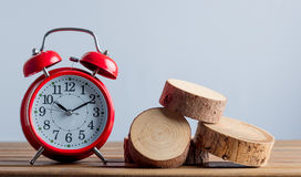 Alarm clock and tree cutted trunk on grey background Stock Photos