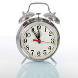 Alarm Clock Urgency. Old fashioned vintage mechanical alarm clock on white background with reflection, pointing five to twelve as a concept of urgency and Royalty Free Stock Images