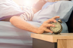 Alarm clock for wake up. The man lying in bed is reaching out to mute the alarm clock Royalty Free Stock Images