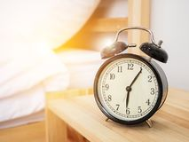Alarm clock , wake-up time concept : Retro alarm clock. With five minutes past six o`clock in the morning on wooden bed side table with white bed sheet and Stock Images