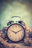 Alarm clock in a wastepaper Royalty Free Stock Image
