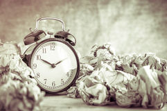 Alarm clock in a wastepaper concept Stock Image
