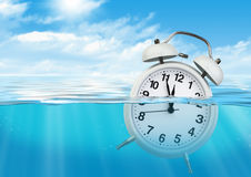 Alarm clock in water, waste of time concept. Clock in water, waste of time concept stock photos