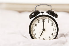 Alarm clock on white bed Royalty Free Stock Photos