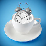 Alarm clock in the white cup on blue background Royalty Free Stock Image