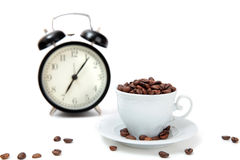 The alarm clock and white cup filled by coffee beans Royalty Free Stock Image