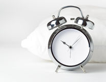 Alarm clock and white pillow Stock Images