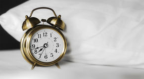 Alarm clock and white pillow Royalty Free Stock Photography