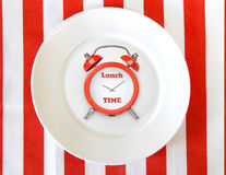 Alarm clock on white plate.Lunch time concept background. Dinner meal break conceptual icon Stock Photography