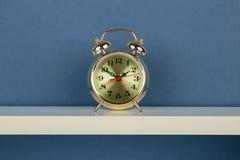 Alarm clock on white  shelf on blue wallpaper Stock Photo