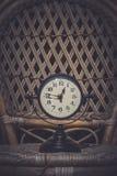 Alarm clock on wicker chair. stock image