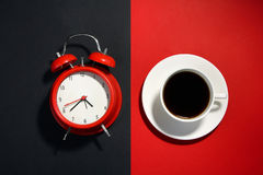 Alarm clock. Windup alarm clock red and white coffee Cup on a black and red background Stock Photo