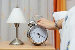 Alarm clock with woman in bed royalty free stock photos