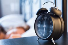 Alarm Clock and Woman Sleeping in the Morning Royalty Free Stock Photography