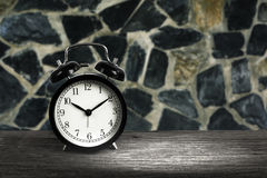 Alarm clock on wood with blurry stone wall in background royalty free stock photos