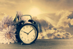 Alarm clock on wood with Golden sky in background Stock Photography