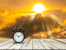 Alarm clock on Wood table and golden sky. Stock Photography