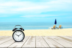 Alarm clock on wood table and sea beach blurred in background Stock Photo