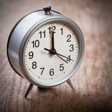 Alarm-clock on wooden surface Royalty Free Stock Photo
