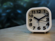 Alarm clock on wooden table with outdoor blur background. Royalty Free Stock Photos