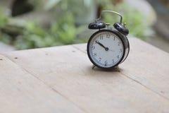Alarm clock on wooden table in Park. Alarm clock  on wooden table in Park Stock Image