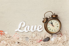 Alarm clock and word Love, net with shells Royalty Free Stock Photography