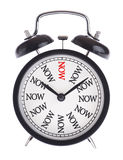 Alarm clock with the word Now. Isolated Royalty Free Stock Photography