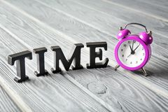 Alarm clock and word TIME composed from letters on wooden background. Time management concept stock image