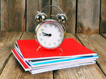 Alarm clock and writing-books . Stock Photography