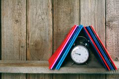 Alarm clock and writing-books on a wooden shelf. Stock Photo