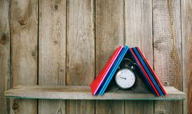 Alarm clock and writing-books on a wooden shelf. Stock Photography