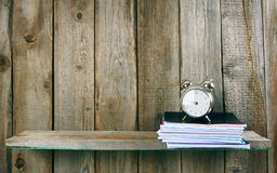 Alarm clock and writing-books on a wooden shelf. Royalty Free Stock Photos