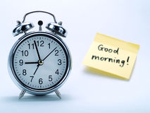 An alarm clock and a yellow note Stock Image