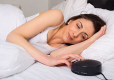Alarm clock. Young woman turning off the alarm clock in the morning royalty free stock photos