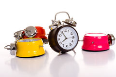 Alarm Clocks. Several brightly colored traditional alarm clocks thrown on a white background stock photos
