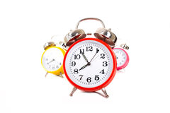 Alarm Clocks. Several brightly colored traditional alarm clocks thrown on a white background royalty free stock images