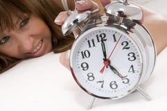 Alarm-clocks rings. Tired woman wakes up because her alarm-clocks rings Stock Image