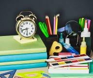 Alarm clocks and school supplies Stock Photos