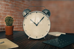 Alarm on desktop. Glossy alarm clock on wooden desktop with cactus, calculator and other items on red brick wall background. 3D Rendering Stock Image