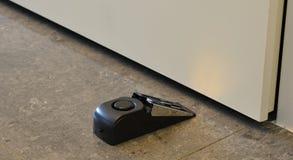 Alarm doorstop. Mobile door alarm placed behind a door stock photo