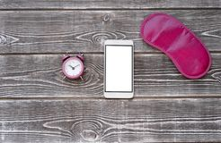 Alarm, eye mask for a pink sleep, a smartphone in white with a white screen. On a wooden background royalty free stock photography